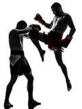 Two men exercising thai boxing silhouette. Two caucasian  men exercising thai boxing in silhouette studio  on white background Royalty Free Stock Photos