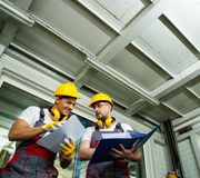 Two men on a factory. Two workers  in a factory control room reading documentation Royalty Free Stock Image
