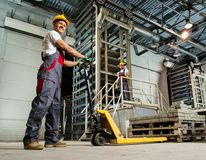Two men on a factory. Young worker moving paving stones with pallet truck on a factory royalty free stock photography