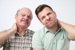 Two men father ans son suffering with neck pain royalty free stock photo