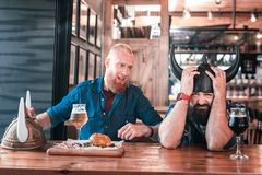 Two men feeling awful after watching football game in the pub. Awful feeling. Two men feeling awful after watching football game in the pub and losing of their royalty free stock images