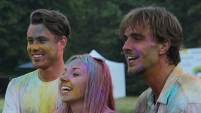 Two men and female posing for camera and throwing powder paint in the air. Stock footage stock video