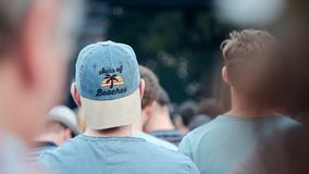 Two men in a festival crowd B. Backside of two man at a summer festival enjoying a live concert Stock Photo