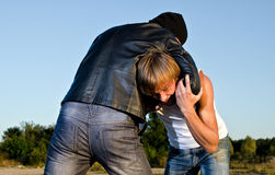 Two men fight outdoors. Robbery concept royalty free stock image
