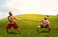 Two men fighting for sausages Stock Photos
