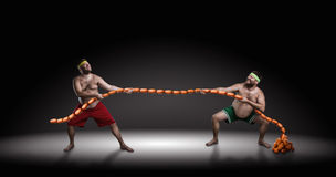 Two men fighting for sausages Royalty Free Stock Photos