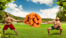 Two men fighting for sausages Royalty Free Stock Images