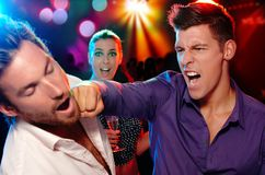 Two men fighting for a woman in nightclub. One men hitting another on the face in nightclub, women watching from background Royalty Free Stock Image