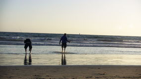 Two Men fishing at beach. Two men fish off the beach as another man jogs by stock footage