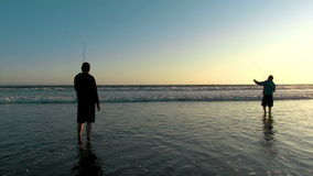 Two Men fishing at beach. Two men fish off the beach as another man jogs by stock video