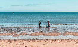 Two men Fishing on Hornsea Beach stock photos