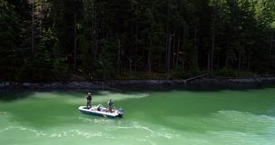 Two men fishing in the river while sailing in the boat on a sunny day 4K 4k. Aerial view of two men fishing in the river while sailing in the boat on a sunny day stock video