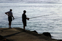 Two men fishing in the sea. Stock Photography