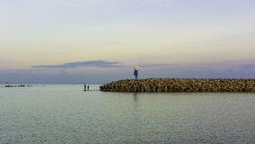 Two men fishing in the sea near lighthouse Royalty Free Stock Photos