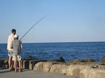 Two men fishing at seashore Stock Image