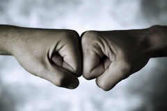 Two men fist bumping. Closeup of the hands of two young caucasian men who are bumping their fists Royalty Free Stock Photo