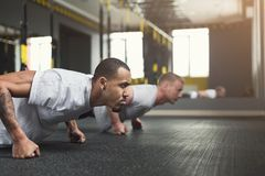 Two men fitness workout, push ups or plank. Multiethnic men workout in fitness club. African-american and caucasian guys making plank or push ups exercise stock photo
