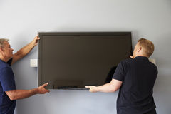 Two Men Fitting Flat Screen Television To Wall Stock Photography