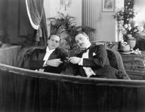 Two men in formal attire sitting together in a theater box Royalty Free Stock Images