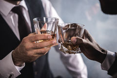 Two men in formal wear clinking whiskey glasses Royalty Free Stock Images