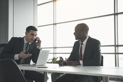 Elegant male people holding business meeting. Two men in formalwear sitting in the office. Caucasian communicating by cellphone and his african partner holding Stock Image