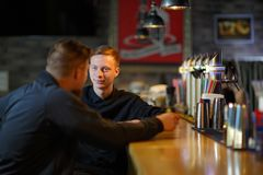 Two men of friends, chatting about something, sitting in a bar behind the bar. Two young men of friends, European appearance, chatting about something, sitting Stock Photography