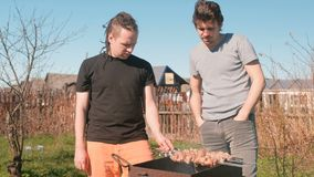 Two men friends cook shashlik meat on top of charcoal grill on backyard. Talking and smiling together. Two men friends cook shashlik meat on top of charcoal stock video footage
