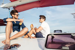 Two men friends drinking beer while resting on the yacht Royalty Free Stock Images