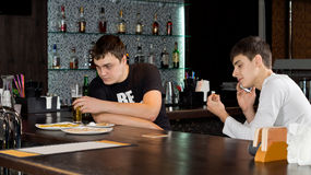 Two men friends having a drink at the bar. Two men friends enjoying themselves having a drink of beer at the bar with one busy having a conversation on his royalty free stock photos
