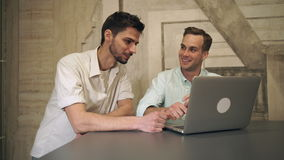 Two men friends looking on the computer and laughing. Happy man watching funny video on the laptop. Casual males spend time stock footage