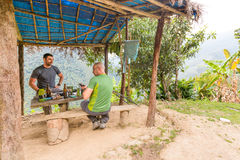 Two men friends resting eating jungle shelter, Bolivia hiking. Two guys friends backpackers resting eating taking break jungle shelter mountains, El Choro trek Royalty Free Stock Photography