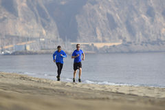 Two men friends running together on beach sand coast mountain bachground in healthy lifestyle concept Royalty Free Stock Photos