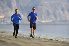 Two men friends running together on beach sand coast mountain bachground in healthy lifestyle concept Royalty Free Stock Photography