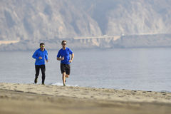 Two men friends running together on beach sand coast mountain bachground in healthy lifestyle concept Royalty Free Stock Photo