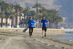 Two men friends running together on beach sand coast mountain bachground in healthy lifestyle concept Stock Images