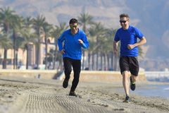 Two men friends running together on beach sand with palm trees m Royalty Free Stock Photography