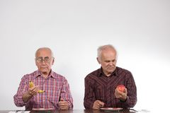 Two men with fruits, banana and apple royalty free stock photo