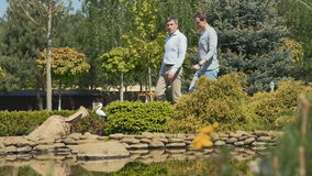 Two men in the garden near the pond. Slowmotion. Two handsome men move across the blooming garden near the pond. Men stop and the attractive man points with the stock video footage