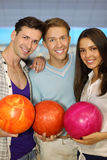 Two men and girl hold balls in bowling club Stock Photos