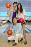 Two men and girl hold balls in bowling club Stock Images