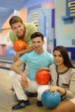 Two men and girl hold balls in bowling club Royalty Free Stock Photo