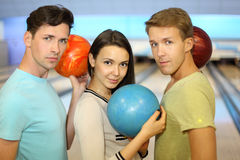 Two men and girl hold balls in bowling club Stock Photo