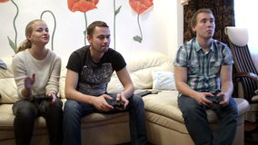 Two men and girl playing video game. Two men and girl sitting on the sofa and playing video game using gamepads. Girl has surprising expression on the face stock video footage