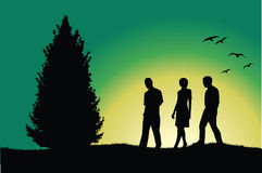 Two men and girl walking on hill near tree Stock Images