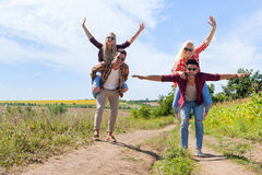 Two men girlfriends piggyback rides cheerful couple young friends Stock Images