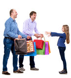 Two men giving shopping bags to a girl Royalty Free Stock Images