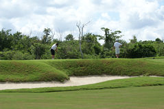 Two Men Golfing. With a sand trap in the foreground on a golf course in Cozumel Mexico royalty free stock images