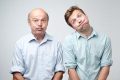 Two men grimacing, inflating cheeks, holding breath. Father and son having fun. Studio shot royalty free stock images