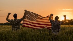 Two men happily raise the American flag over a field of wheat at sunset. 4th of july concept.  stock photo