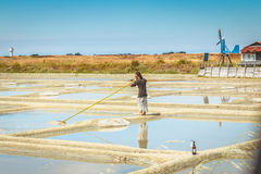 Two men harvest salt in the traditional way in the salt marshes Royalty Free Stock Photos